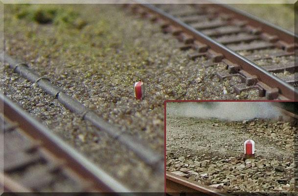 Weichen-Grenzzeichen kennzeichnen die Stelle, bis zu der Fahrzeuge ohne Verletzung des Lichtraumprofils abgestellt werden dürfen. Ich hab' sie selber (aus Stecknadeln) gebaut/bemalt. Ein kleines Vorbildfoto - zum Vergleich - ist mit im Bild zu sehen.