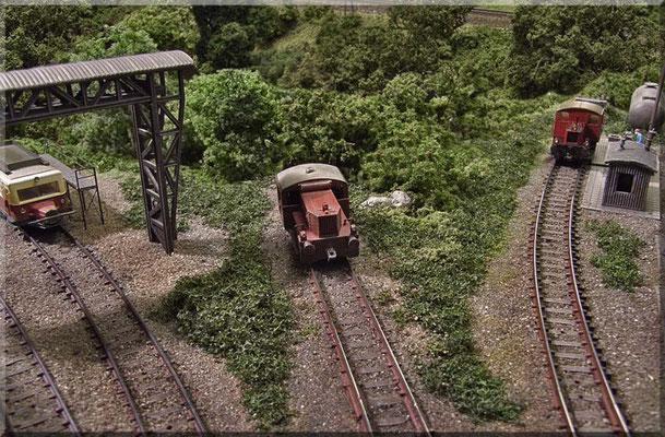 """Diverse """"Drehscheiben-Stumpfgleise"""" im Bahnbetriebswerk. Von links nach rechts: Der Wismar-Bus (das """"Schweineschnäuzchen"""") an der Arbeitsbühne von Beier, die Köf II auf einem Abstellgleis, die Kö I an der Zapfsäule. Der Bockkran stammt von Faller."""