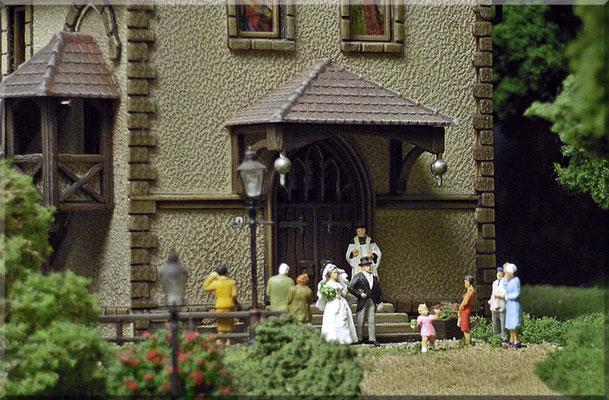 """Eine Großaufnahme des frisch getrauten Paares, mit Priester und einigen Gästen. Der """"Rosenbusch"""" im Vordergrund besteht (ganz simpel) aus einem Foliage-Klumpen, mit roter Farbe betupft. Die schönen Gaslaternen sind Bausätze von Modellbau-Mayerhofer."""