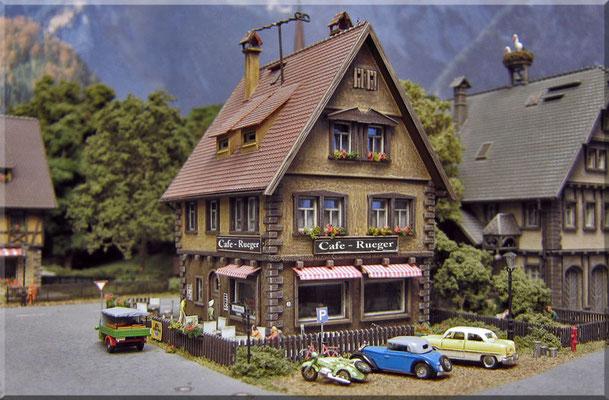 Das Cafe-Rueger ist ein beliebter Treffpunkt der Waldbronner Jugend. KFZs, Hydrant, Gullydeckel und Mülltonnen: von Marks Metallmodellclassic´s. Fahrrad, von D.Beier-Modellbau. Gaslaterne: Modellbau Mayerhofer. Figuren: Preiser. Gebäude, von Vollmer.