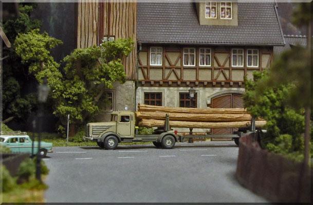 Ein Langholz-Lastwagen aus der Bahnhofsstrasse heraus fotografiert. Hier kommt der große Vorteil einer kleinen Kamera zum tragen. Der Büssing 8000 - mit Echtholz-Ladung ist eines der wenigen Wiking-Modelle auf der Anlage und wurde optisch getunt.