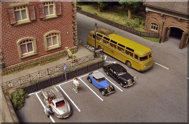 Bahnhofsplatz. Das junge Pärchen bestaunt den Mercedes SL 300. Rechts stehen DKW F 7, MB 190 D Taxi und ein Post-Bus Büssing TU 11. Alle Fahrzeuge und der Kanaldeckel stammen von Marks. Straßenschild und Leuchten von Mayerhofer. Geländer von Weinert.