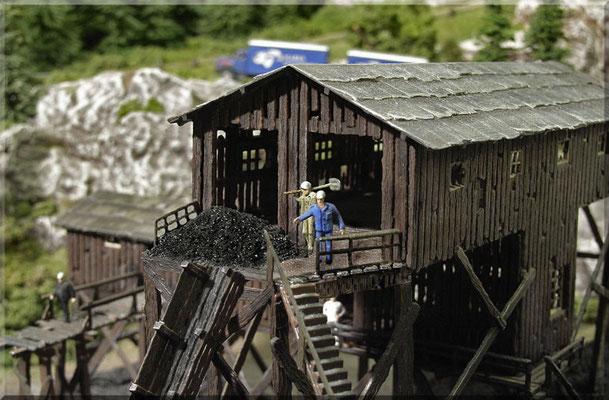 """Mittagspause in der Kohlemine! Echte Knochenarbeit leisten die Männer hier und kriegen mächtig Kohldampf. Sie freuen sich über jede Unterbrechung. Der marode Bretterbau der """"Waldbronner Kohle AG"""" entspricht wohl kaum dem neuesten Sicherheitsstandard."""