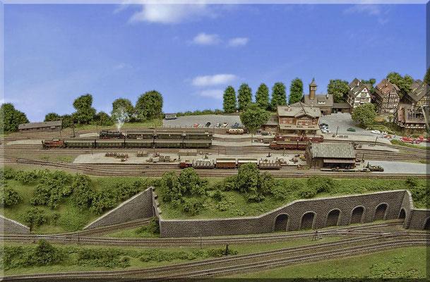 Der gesamte Bahnhofsbereich im Überblick aus der Vogelperspektive. Hier sieht man den Mittelteil des oberen, rechten Anlagenschenkels. Im unteren Bereich ist die zweigleisige Haupt/Paradestrecke und die von ihr abzweigende Nebenbahn zu sehen.