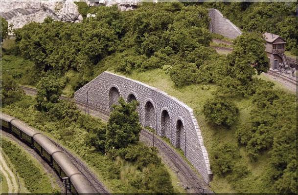 Eine üppige Vegetation und div. Kunstbauten (hier eine Arkadenmauer) sorgen für ein abwechslungsreiches Bild entlang der Strecke.