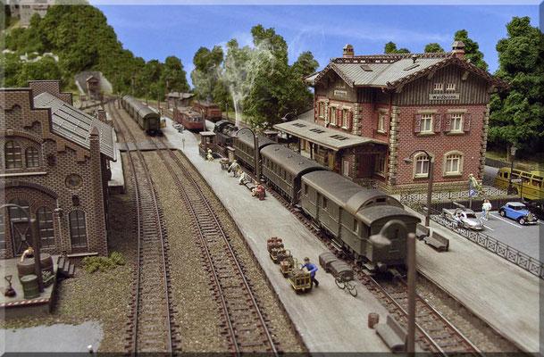 """Blick aus der Gegenrichtung - zur Bahnhofseinfahrt. Im Hintergrund sieht man das kleine Stellwerk und dahinter das Süd/West-Portal des  """"Großen Burgbergs"""". Die im leichten Bogen verlegten Gleise und Eigenbau-Gips-Bahnsteige sind hier gut zu erkennen."""