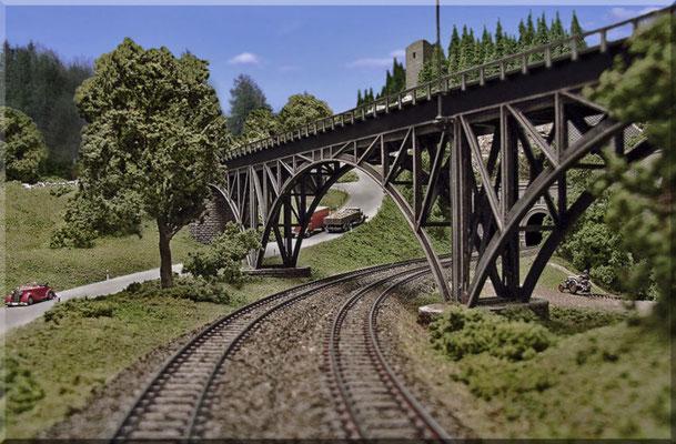 """Die Stahlbogenbrücke aus der """"Lokführer-Perspektive"""". Rechts unter der Brücke: Ein Bauer mit seinem """"Fendt-Dieselroß"""" und einer Egge, beim bearbeiten seines Ackers. Links, die Landstrasse zum """"Kleinen Burgberg""""."""