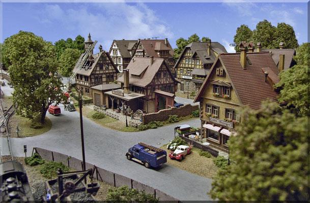 """Blick vom BW auf das Bahnhofsviertel. Straßenbau: Nach einem """"grundierenden Anstrich"""" (Aufquellschutz für's Sperrholz) wurde eine dünne Schicht """"Moltofill"""" aufgetragen, geschliffen, gestrichen (Straßenfarbe von Heki) und nochmals leicht geschliffen."""