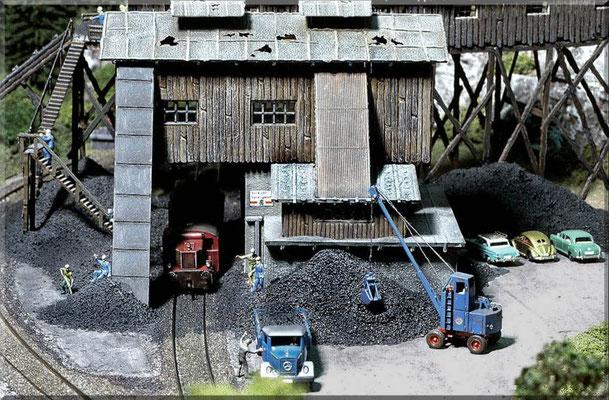 """""""Vorderansicht"""" der Kohlemine mit einer nachgestellten Ladeszene. Die Köf stammt von Arnold, die Figuren von Preiser, der MB-Laster ist ein verbessertes Modell von Wiking, die Pkws sind von Marks, ebenso wie der tolle Fuchsbagger. Gebäude, von Pola."""