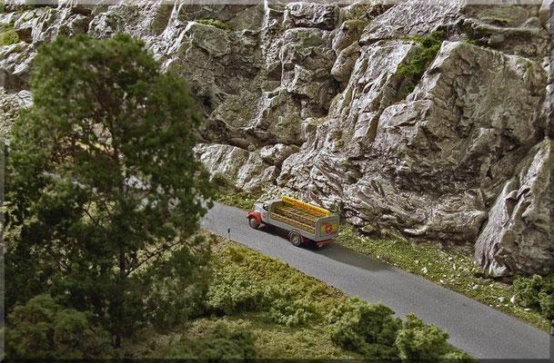 """Alfred Mayr ist mit seinem Sinalco-Getränke-Laster unterwegs ins Nachbardorf. Er hat dort viele Kunden, die schon auf Bier und Limo warten. Vor der gigantischen Felswand des """"Kleinen Burgbergs"""" wirkt der Mercedes Benz 3500 richtig winzig. Auto: Marks."""