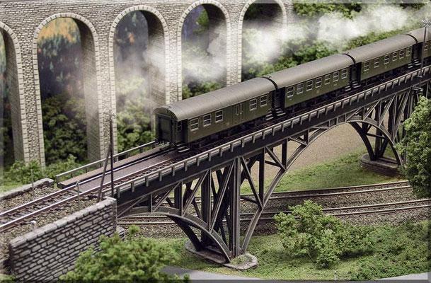 Auf Gitterbrücken ist der Gleiszwischenraum mit einem Riffelblech abgedeckt. Schneepflug-Tafeln und Kilometerstein: Paul Petau. Telegrafenmast: Weinert. Die Schneepflug-Tafeln zeigen dem Lokführer an, dass ein vorhandener Pflug angehoben werden muss.