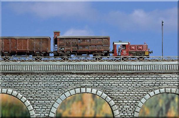 Der Lokführer steuert seine Köf II (Arnold-Modell) in schwindelerregender Höhe über das Steinbogen-Viadukt. Die Fahrzeuge wurden mit Revell-Farben gealtert.