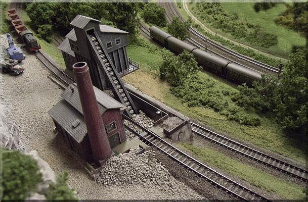 Die V 36 (Minitrix) hat ihre Kipploren (Arnold) bereits geleert und verlässt den Steinbruch im Schiebebetrieb. Rechts oben sieht man die Gleise der Haupt- und Nebenbahn.