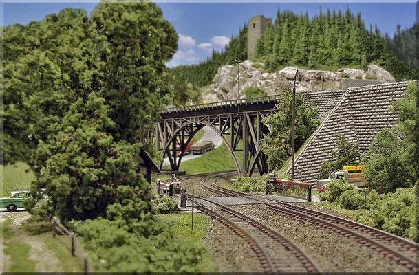 """Blick über den Bahnübergang zur Stahlbogenbrücke (Faller-Modell) , auf der die Nebenbahn die Hauptstrecke überquert. Im Hintergrund: Die Bergstrasse zum """"Kleinen Burgberg"""" und die Burgruine (Umbau aus Pola-Teilen). Telegrafenmast: Weinert."""