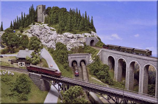 """Der """"Kleine Burgberg"""" aus Richtung der beiden Brückenbauwerke gesehen. Das doppelte Tunnelportal bildet die Aus/Einfahrt des Gleiswendels."""