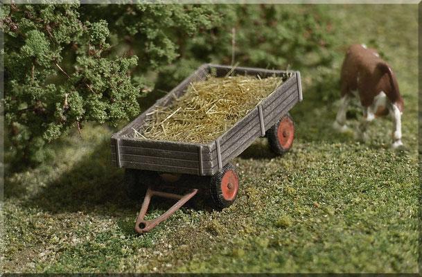 Großaufnahme eines landwirtschaftlichen Anhängers - mit Heu beladen. Der schöne Anhänger ist mal wieder ein detailliertes Modell von Marks Metallmodellclassic's, die Kuh stammt vom Hersteller Preiser und die Begrünung von Heki und Woodland Scenics.