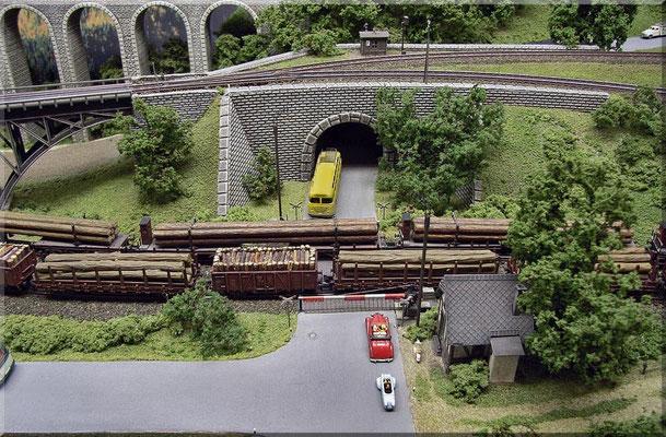 """Der Bahnübergang aus der Vogelperspektive. In der Umgebung von """"Waldbronn"""" gibt es viel Wald und damit auch jede Menge Holztransporte. Im Hintergrund ist der """"Steinbogen-Viadukt"""" der Nebenbahn zu sehen. Autos: Marks ; Fernsprech-Bude: Arnold"""