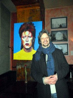 """Der Maler Willi Büsing vor dem von ihm gemeinsam mit Jennifer Jennsel gemalten Bild """"Bowie's Sparkle"""" im Café """"Neues Ufer"""" in Berlin-Schöneberg"""