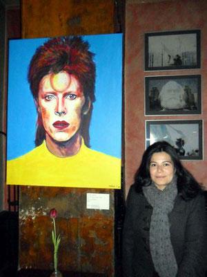 """Die Malerin Jennifer Jennsel vor dem von ihr gemeinsam mit Willi Büsing gemalten Bild """"Bowie's Sparkle"""" im Café """"Neues Ufer"""" in Berlin-Schöneberg"""