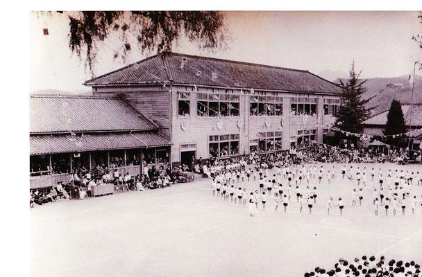 安心院小学校の二代前の校舎での運動会の様子です。昭和20年代後半から30年代後半の写真。当時は運動場を「コの字」に木造校舎が取り囲み、保護者や地域の人たちは皆、校舎の中からの応援でした。翻る万国旗を支える大柳の枝が左側上部に見えます。大柳も現在は3世となっています。