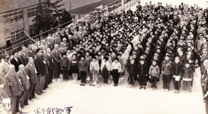昭和36年、念願の鉄筋コンクリート3階建ての校舎が新築しました。場所は新築校舎の屋上。今では考えられない教育環境でした。写真左手前は当時の県知事木下郁様。右側前列が安心院町長矢野武夫様。5.6年生の児童が参列しています。当時は全校800名。とても活気がありました。