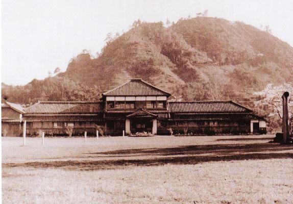 騰宮学館は、現在の妻垣神社の境内の中にありました。神社の南側に広がる広場の南側に建っていました。後ろに聳えるのは「竜王山」です。右の鳥居は、忠魂碑の前に建っていました。校舎の前には、とても広いグランドがありました。