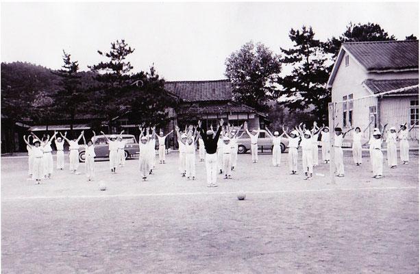 昭和30年代後半頃の安心院中学校の体育の授業の様子です。当時の中学校は、今の亀の井ホテル(現在のAZホテル)の建っている場所にありました。このころは、バレーボールやバスケットボールなどは屋外で行われていました。写真には、バレーボールのネットが写っています。