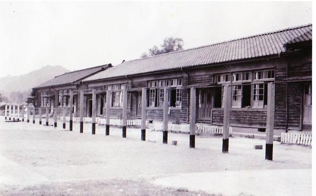 木造校舎の様子です。この頃多くの学校が運動場を「コの字」型で囲った校舎でした。運動会では、観覧者は校舎の中から応援していました。左手の山は竜王山です。