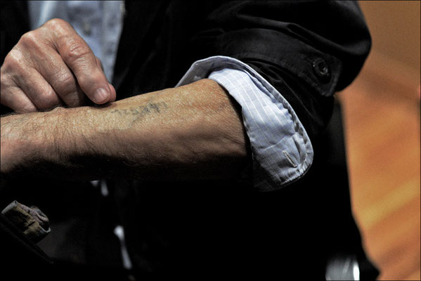 Russian survivor shows his tattoo of Auschwitz