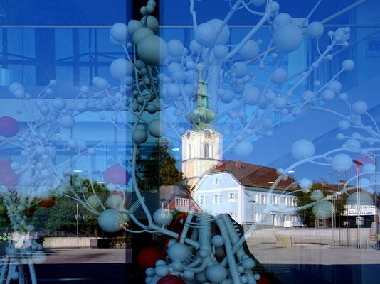 Kirche und 44er Haus spiegeln sich in der Gemeindehaus-Fassade