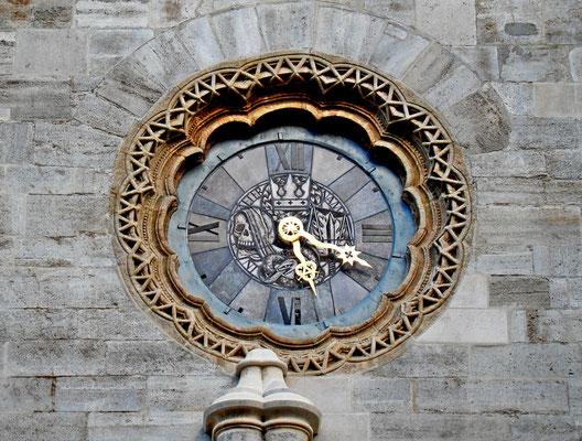 die Uhr links nebem dem Riesentor mit Sonnensymbol, Totenschädel, Waage des Jüngsten Gerichts mit Richtschwert und darunter das männliche Symbol