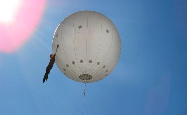 der Bubble Man ... eine lebensgroße Figur schwebt an einem Heliumballon über der Stadt