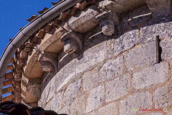 Quatre modillons, un damier, une tête couverte d'un capuchon, une tête de cochon, tête entourée de deux mains; vestige d'une meutrière en croix pattée. Eglise Saint-André, Cénac. 10/02/2018