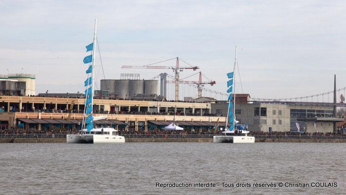 Deux catamarans de la parade passent devant le hangar 16, auprès du quai et donc de la foule. Bordeaux, samedi 16 mars 2013