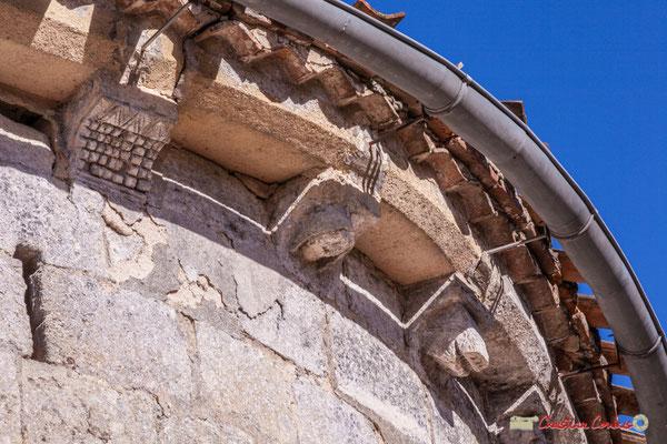 Vestige d'une meutrière en croix pattée; trois modillons, un damier, une tête couverte d'un capuchon, une tête de cochon. Eglise Saint-André, Cénac. 10/02/2018