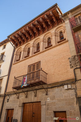 Palais des París Iñiguez Abarca, Rez-de-chaussée en pierre, portail surmonté d'un linteau. Etages en briques. Balcon à balustrade sur des consoles d'applique forgées.  Second étage, galerie de petits arcs en plein cintre. Sangüesa, Navarra