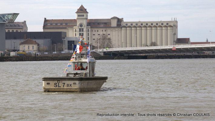 Un des bateaux de la parade sur fond des Grands Moulins de Bordeaux. Gabare les Deux Frères, Bordeaux, samedi 16 mars 2015