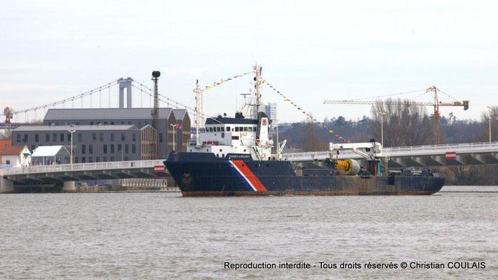 Un bateau des phares et balises, le baliseur Gascogne, remonte le fleuve pour passer non loin des hangars. Bordeaux, samedi 16 mars 2013
