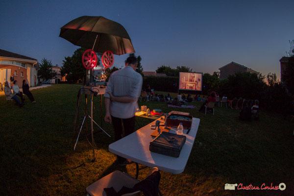 Le film-jockey sous le parasol/parapluie du projecteur 16mm. Association Monoquini, cinéma plein air à Cénac. 06/07/2018
