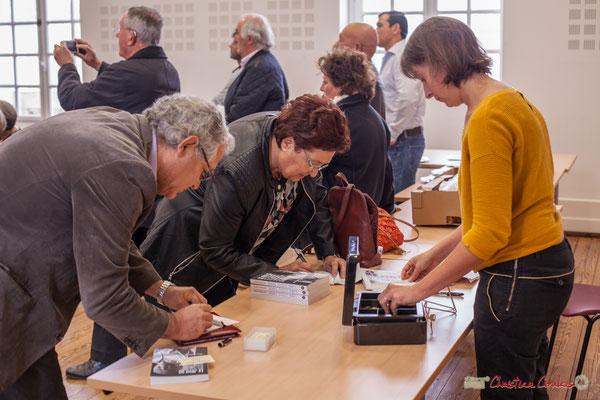 """Vente du livre par la libraire, Sophie, L'éco-libri, Créon. Sortie et dédicace du livre """"Le jour où..."""" de Jean-Marie Darmian. Salle citoyenne, Créon. 14/10/2017"""