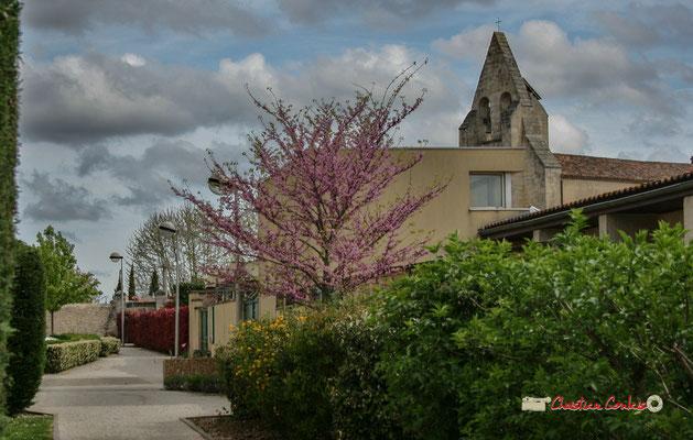 Le mur-clocher de l'église Saint-André et les abords végétalisés du groupe scolaire. Cénac, 14/04/2009