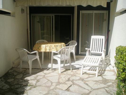 Terrasse et salon de jardin vus depuis la pelouse