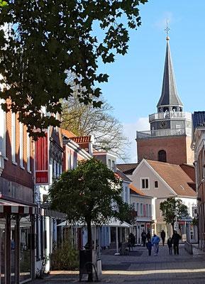 Zahlreiche Einkaufsmöglichkeiten gibt es in der Fußgängerzone; im Hintergrund: der Turm der Lambertikirche.