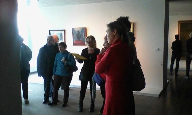 Photo de la guide et d'un groupe de visiteurs lors de la visite des œuvres d'art belge de l'expo Belfius