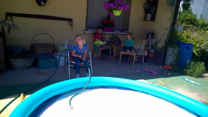 Die Poolsaison wird eröffnet, geduldig füllt Rachelle das Wasser ein.
