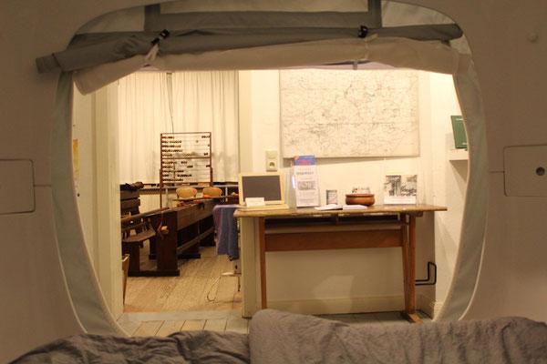 """Aus dem gemütlichen """"sleep Cube"""" schauen die Gäste direkt in das historische Klassenzimmer mit seinen hölzernen Schulbänken, Schiefertafeln und Lehrerpult"""
