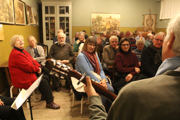 """Publikum: Zu den Gitarrenklängen von Hans-Peter Lindner sagt das Publikum im historischen Klassenzimmer aus voller Kehle auch von """"Herrn Pastor sien Kauh""""."""