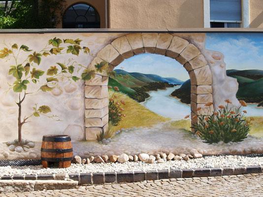 Illusionsmalerei im Garten, Torbogen mit Landschaft und Weinrebe