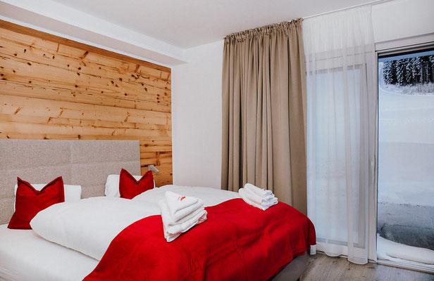 Schlafzimmer 1 Hochwurzen Suite: für 2 Personen mit Blick zur Piste und Ausgang zur Terrasse