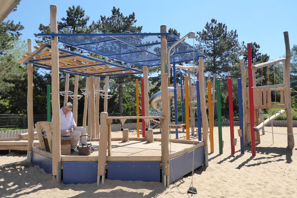 inklusiver Pavillon mit Sandbaustelle, Sitzpoller, Bank, Schattendach